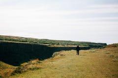 Alleinmann, der auf die isländische Landschaft geht Stockbilder
