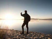 Alleinmann an der Küste unter Verwendung des Handys, zum von selfie Foto mit dem Meer hinter ihn zu machen Lizenzfreie Stockfotos