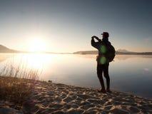 Alleinmann an der Küste unter Verwendung des Handys, zum von selfie Foto mit dem Meer hinter ihn zu machen Lizenzfreie Stockbilder