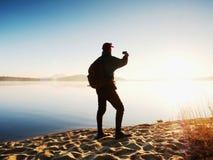 Alleinmann an der Küste unter Verwendung des Handys, zum von selfie Foto mit dem Meer hinter ihn zu machen Stockfotos
