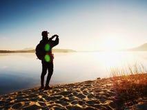 Alleinmann an der Küste unter Verwendung des Handys, zum von selfie Foto mit dem Meer hinter ihn zu machen Stockbilder