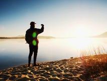 Alleinmann an der Küste unter Verwendung des Handys, zum von selfie Foto mit dem Meer hinter ihn zu machen Stockbild