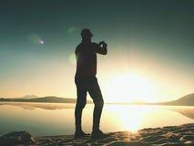 Alleinmann an der Küste unter Verwendung des Handys, zum von selfie Foto mit dem Strand hinter ihn zu machen Lizenzfreie Stockfotografie