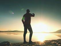 Alleinmann an der Küste unter Verwendung des Handys, zum von selfie Foto mit dem Strand hinter ihn zu machen Lizenzfreies Stockfoto