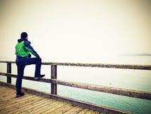 Alleinmann am Handlauf, nebelhafter Morgen des Herbstes auf Seepier deprimierend Stockfoto
