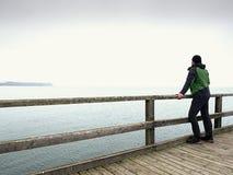 Alleinmann am Handlauf, nebelhafter Morgen des Herbstes auf Seepier deprimierend Stockfotos