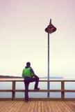 Alleinmann am Handlauf, nebelhafter Morgen des Herbstes auf Seepier deprimierend Lizenzfreie Stockfotografie