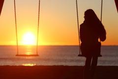 Alleinschwingen der allein stehenden Frau auf dem Strand