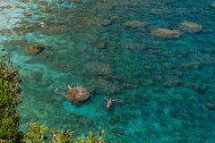 Alleinstehende Frau legt auf das schöne aquamarine haarscharfe Wasser im Entspannung, Draufsicht von der Höhe stockbilder