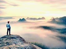 Alleinwanderer im roten Kappenstand auf Spitze des Sandsteinfelsens in den Felsenreichen parken und aufpassend über den Nebel Stockfotografie