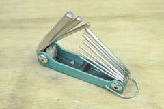 Allen-Schlüssel oder Inbusschlüssel im Holztischhintergrund Stockfotos