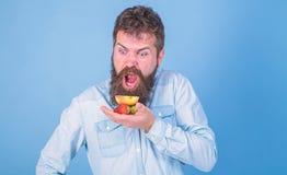 Allen voor me Gebaarde Hipster houdt aardbeien en appel op palm Hongerige de mens eet aardbeien en het appelfruit behandelt stock afbeelding