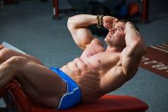 Allenamento adatto dei muscoli addominali del treno del torso dell'ascensore dell'uomo alla palestra Fotografia Stock