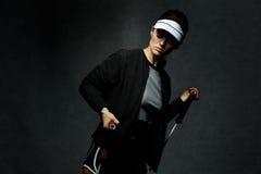 Allenamento adatto della donna con la banda di resistenza contro fondo scuro Fotografia Stock