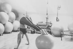 Allenamento, addestramento, attività Ragazza nell'addestramento degli abiti sportivi sul fitball in palestra Fotografia Stock Libera da Diritti