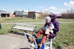 Allenamento all'aperto sorridente felice della bambina e della madre insieme sull'istruttore fuori nel parco naturale in anticipo Fotografie Stock Libere da Diritti