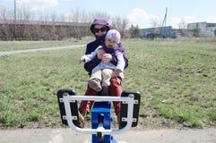 Allenamento all'aperto sorridente felice della bambina e della madre insieme sull'istruttore fuori nel parco naturale in anticipo Immagine Stock Libera da Diritti