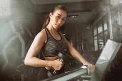 Allenamento asiatico della ragazza di forma fisica che solleva una testa di legno nella palestra Fotografie Stock Libere da Diritti