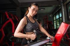 Allenamento asiatico della ragazza di forma fisica che solleva una testa di legno nella palestra Fotografia Stock