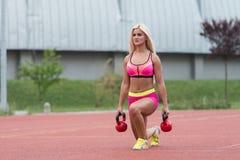 Allenamento atletico della donna con il bollitore Bell all'aperto Immagini Stock Libere da Diritti