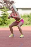 Allenamento atletico della donna con il bollitore Bell all'aperto Immagine Stock