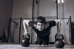 Allenamento bello alla palestra, esercizio dell'uomo forte di piegamento sulle braccia di forza con Kettlebell Immagini Stock