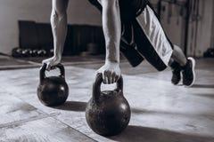 Allenamento bello alla palestra, esercizio dell'uomo forte di piegamento sulle braccia di forza con Kettlebell Fotografia Stock