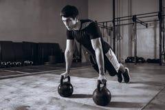 Allenamento bello alla palestra, esercizio dell'uomo forte di piegamento sulle braccia di forza con Kettlebell Immagine Stock