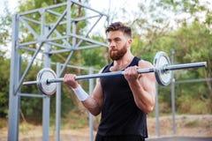 Allenamento bello dell'uomo di forma fisica muscolare con il bilanciere Fotografie Stock