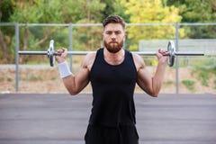 Allenamento bello dell'uomo di forma fisica muscolare con il bilanciere Fotografia Stock Libera da Diritti