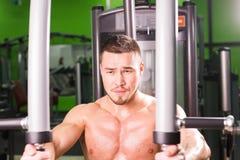 Allenamento bello di sollevamento pesi dell'uomo di forma fisica in palestra Fotografia Stock