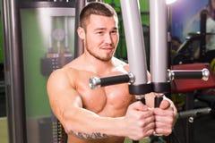 Allenamento bello di sollevamento pesi dell'uomo di forma fisica in palestra Immagini Stock Libere da Diritti