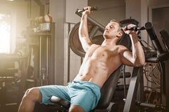 Allenamento bello di sollevamento pesi dell'uomo di forma fisica in palestra Fotografia Stock Libera da Diritti