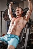 Allenamento bello di sollevamento pesi dell'uomo di forma fisica in palestra Immagine Stock