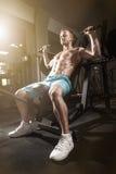Allenamento bello di sollevamento pesi dell'uomo di forma fisica in palestra Immagini Stock
