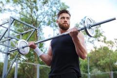 Allenamento bello muscolare dell'uomo con il bilanciere Immagine Stock