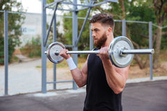 Allenamento bello muscolare dell'uomo con il bilanciere Fotografia Stock