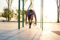 allenamento con le cinghie della sospensione nella palestra all'aperto, in uomo forte che si preparano presto nella mattina sul p Fotografia Stock Libera da Diritti