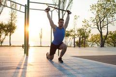 allenamento con le cinghie della sospensione nella palestra all'aperto, in uomo forte che si preparano presto nella mattina sul p Fotografia Stock