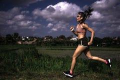 Allenamento corrente di serie del corridore di addestramento asiatico atletico della donna che lavora aria aperta dura sul fondo  Fotografia Stock Libera da Diritti