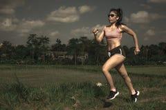 Allenamento corrente di serie del corridore di addestramento asiatico atletico della donna che lavora aria aperta dura sul fondo  Immagini Stock Libere da Diritti