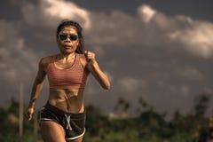 Allenamento corrente di serie del corridore di addestramento asiatico atletico della donna che lavora aria aperta dura sul fondo  Immagine Stock Libera da Diritti