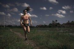 Allenamento corrente di serie del corridore di addestramento asiatico atletico della donna che lavora aria aperta dura sul fondo  Fotografie Stock