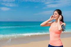 Allenamento corrente sorridente della donna graziosa sulla spiaggia Immagini Stock Libere da Diritti