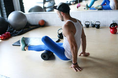 Allenamento del giovane in club in buona salute Esercizio di lavoro dell'uomo per le gambe Fotografia Stock Libera da Diritti