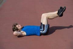 Allenamento dell'uomo con l'ente muscolare che fa gli esercizi per addominale Fotografia Stock