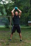 Allenamento dell'uomo di esercizio dell'oscillazione di Kettlebell di forma fisica all'aperto Fotografia Stock