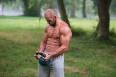 Allenamento dell'uomo di esercizio dell'oscillazione di Kettlebell di forma fisica all'aperto Fotografia Stock Libera da Diritti