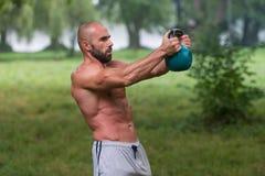 Allenamento dell'uomo di esercizio dell'oscillazione di Kettlebell di forma fisica all'aperto Fotografie Stock Libere da Diritti