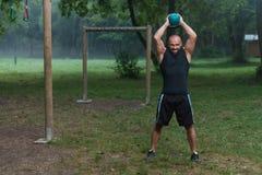 Allenamento dell'uomo di esercizio dell'oscillazione di Kettlebell di forma fisica all'aperto Immagini Stock